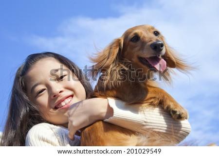 Girl hugging a miniature dachshund - stock photo