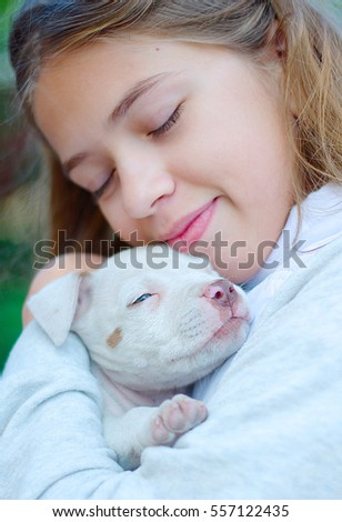 girl hugging a puppy American pit bull Terrier