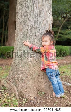 Girl hugging a tree - stock photo