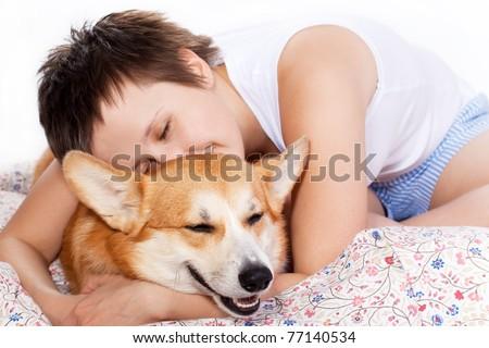 Girl hugging a welsh corgi pembroke dog in bed - stock photo