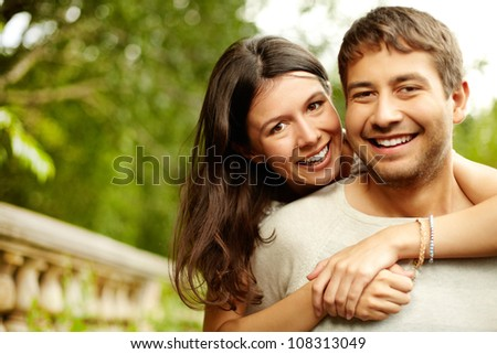 Girl hugging his boyfriend, both looking at the cam and smiling - stock photo