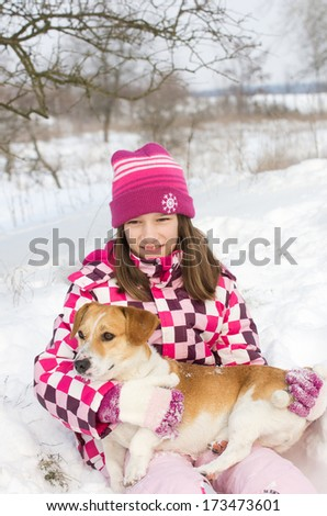 Girl hugs her dog on snow during winter walk in nature - stock photo