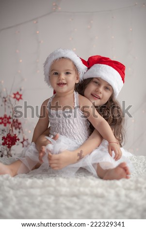 Girl hugs her little sister, both wearing red Christmas caps and smile,  - stock photo