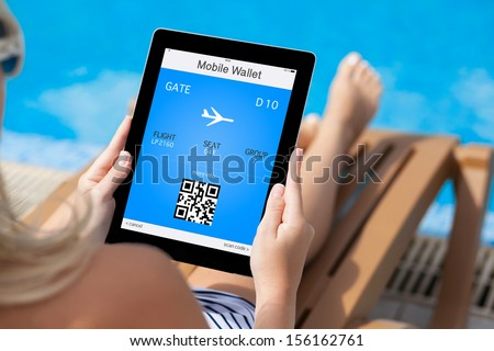 girl in a bathing suit lying on a deck chair by the pool and holding a tablet computer with mobile wallet and plane ticket on a screen