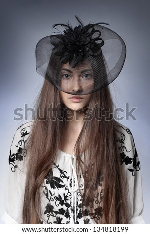 girl in a beautiful black hat with feathers - stock photo