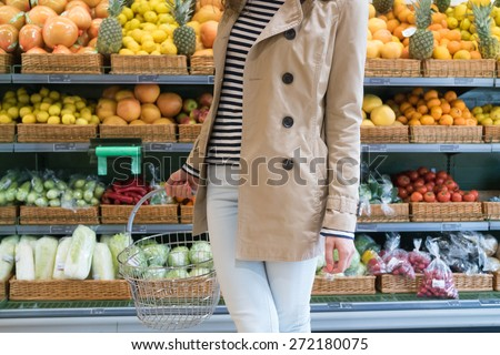 Girl in a beige coat and light blue jeans in the grocery store holding a shopping basket. In the background you can see the showcase of vegetables and fruits. - stock photo