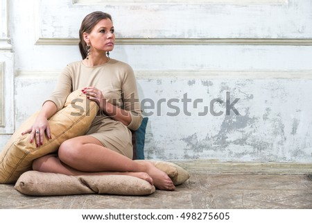 girl in a beige dress sitting on cushions in a room in a grunge style