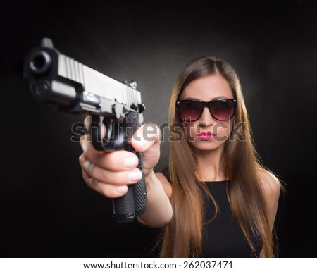 girl in a black dress and Sunglasses holding a gun - stock photo