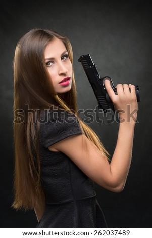 girl in a black dress holding a gun - stock photo