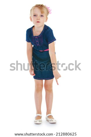 Girl in a blue denim dress shows the index finger on the floor on a white background.The concept of a child learning and development.