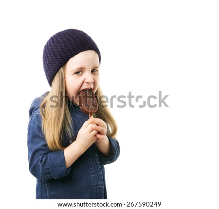 girl in a blue hat and coat eating ice cream on a white background - stock photo