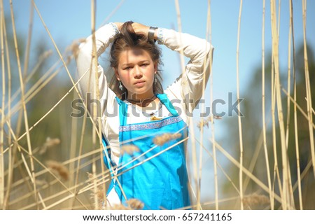 Girl in a blue sundress in a field of tall dry grass