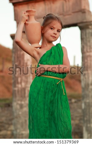 Girl in a bright emerald green dress standing in the ruins of the ancient city of Pantikapaion in the role of the Greek goddess - stock photo
