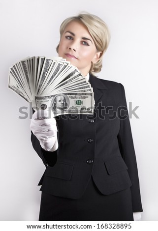 Girl in a business suit keeps dollars fan in his hand