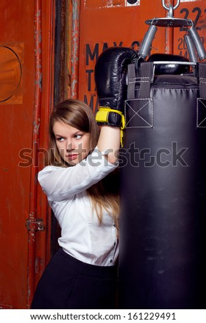 Girl in a business suit near punch bag - stock photo