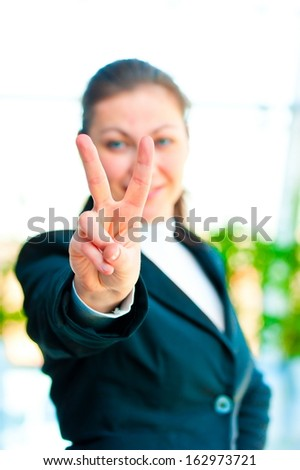 Girl in a business suit showing gesture ���«victory hand���» - stock photo