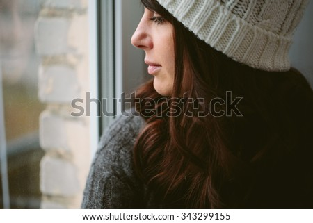 Girl in a cap looks out of the window closeup photo. - stock photo