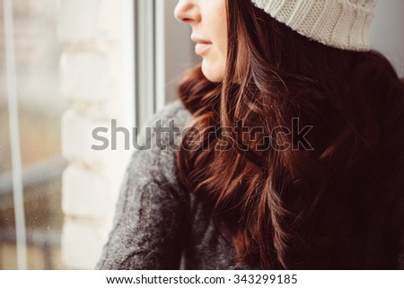 Girl in a cap looks out of the window. Half face closeup photo. - stock photo