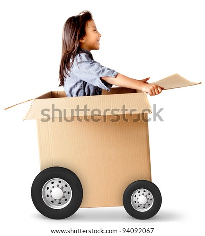Girl in a car made of cardboard box - delivery on wheels - stock photo