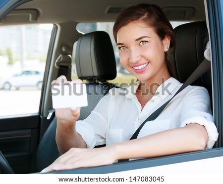 girl in a car showing an empty white card for your message  - stock photo