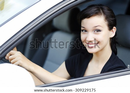 Girl in a car smiling to you. - stock photo