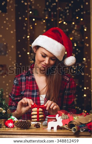 Girl in a checkered shirt and Santa hat bandages cookies red ribbon