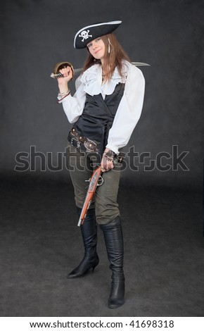 Girl in a costume of the sea pirate on a black background with a sabre and a pistol