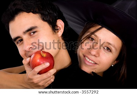 girl in a couple holding the apple of temptation for the man - isolated over a black background - stock photo