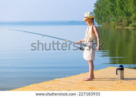 Girl in a dress and a hat with a fishing rod fishing from the pier