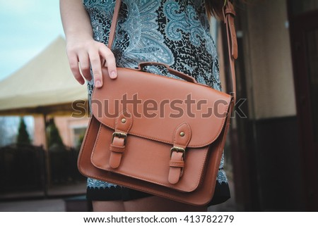 girl in a dress holding a brown bag bag, fashion, closeup - stock photo