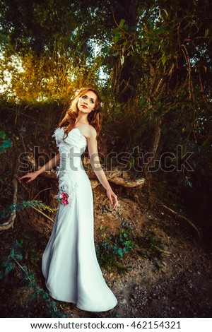 girl in a dress in the evening at the tree