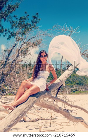 girl in a dress on a dry tree on the beach of La Digue Seychelles - stock photo