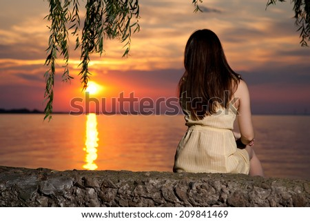 girl in a dress on the beach at sunset - stock photo