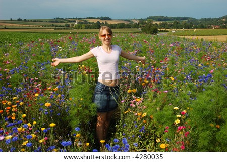 Girl in a field with vibrant flowers - stock photo
