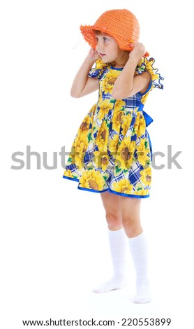 girl in a flowered dress orange hat isolated on white background.The concept of development of the child, the child's upbringing.