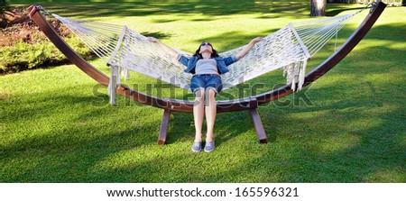 Girl in a hammock in a summer park - stock photo