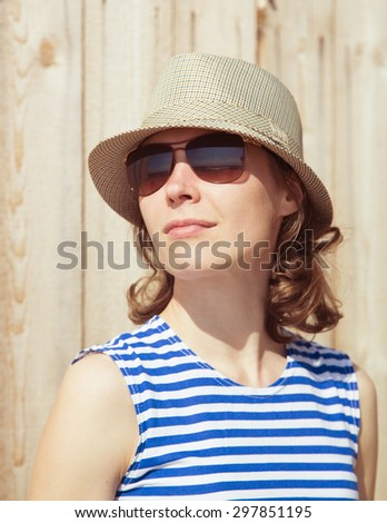 Girl in a hat and sunglasses at the wooden fence.