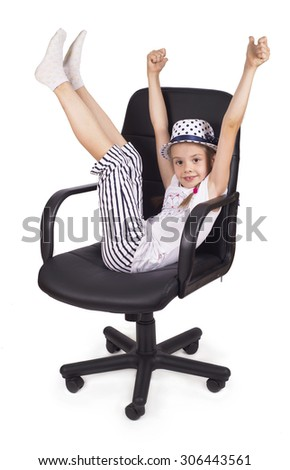girl in a hat raises her arms and legs up, sitting on a black office chair. Isolated - stock photo