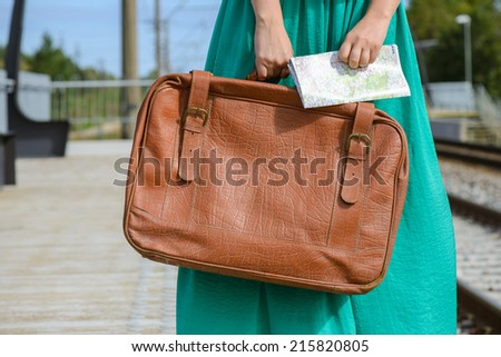 Girl in a holding a map and suitcase at station - stock photo