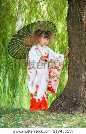 girl in a Japanese kimono with umbrella standing under the willow