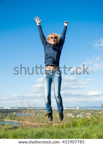 Girl in a jump over a cliff with views of the city.