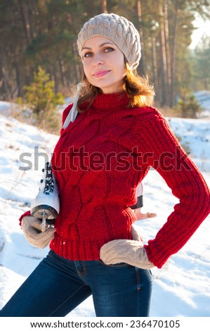 Girl in a knit sweater and hat with skates outdoors in winter