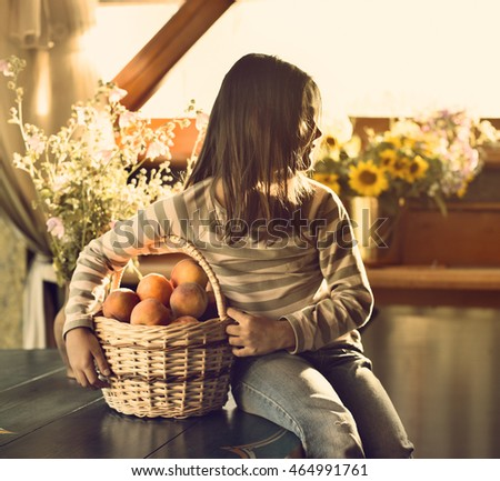 Girl in a light room and a fruit basket.