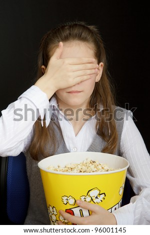 girl in a movie theater closes her eyes - stock photo