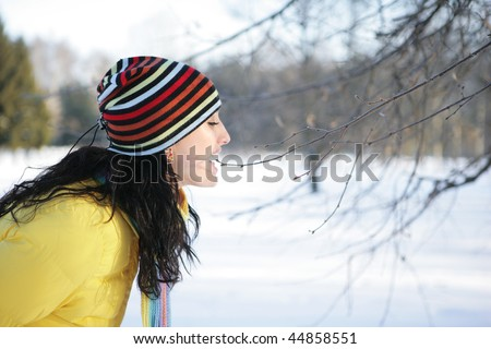 Girl in a park in the yellow jacket bites branch