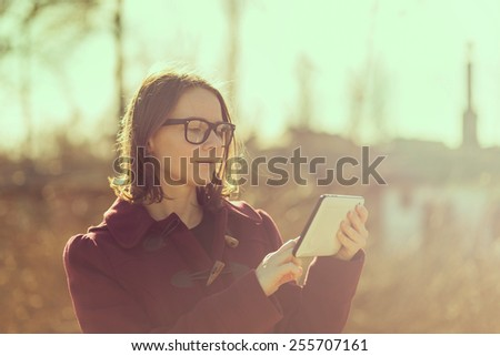 Girl in a park surfing the internet on a tablet  - stock photo