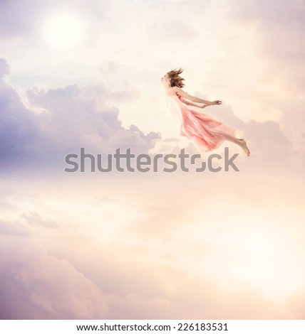 Girl in a pink dress flying in the sky. Serenity. - stock photo
