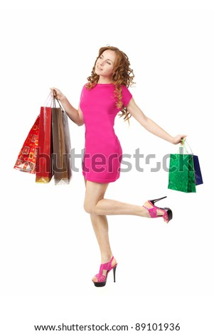 girl in a pink dress with shopping bags in studio - stock photo