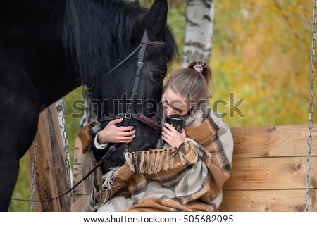 girl in a plaid with a black horse in the autumn under a birch tree on a bench.