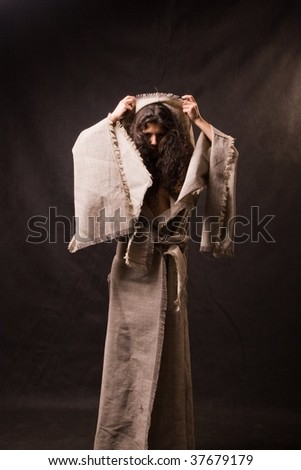girl in a raincoat from a rough fabric is isolated on a black background
